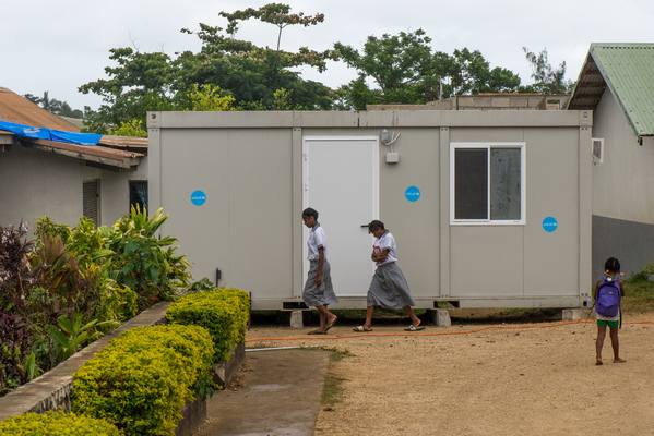 Students from Vila North school in Port Vila walk past an 'office in a box' provided by UNICEF, whose extensive support has made it possible for Vila North to continue providing an education for hundreds of children.