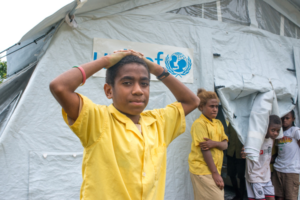 A student from St Joseph school near Port Vila stand outside the tent that has been his classroom since cyclone Pam destroyed part of the school. If not for the shelter supplied by UNICEF, students would have been sent home on a rotating basis.
