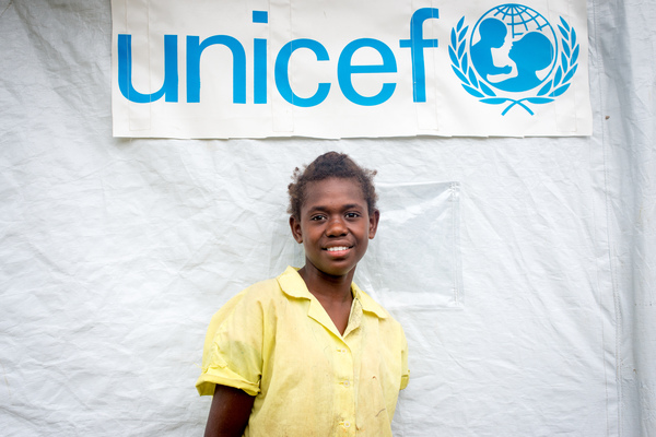 Ellen, a 13 year old student from St Joseph school near Port Vila stands outside the tent that has been her classroom since cyclone Pam destroyed part of the school. If not for the shelter supplied by UNICEF, students would have been sent home on a rotating basis.