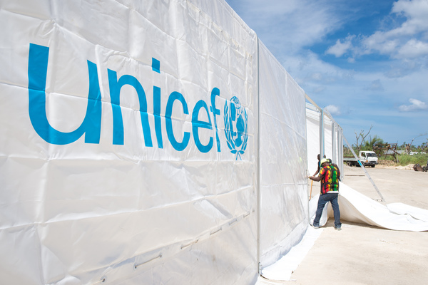 Staff and volunteers wrangle over 90 tonnes of newly arrived emergency supplies at the UNICEF warehouse near Port Vila, Vanuatu. The influx of supplies required the construction of a new temporary storage facility as well.